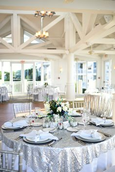 Silver table overlays. Silver chargers, silver chiavari chairs. Elegant, glam, diamond napkin rings, wedding reception.