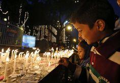 Nueva Delhi India.Niños encienden velas con motivo de la Navidad