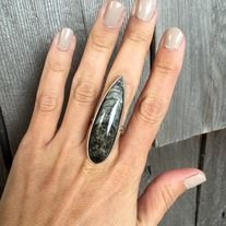 A large stunning large teardrop Orthoceras fossil has been set in sterling silver with a sterling silver ring band handmade from half dome wire. The AAA natural Orthoceras fossil is awesome and rocker chic! This ring is 2 inches long and just over an 1/2 inch long at the widest point of the fossi...