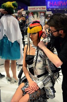"A hairdresser styles his model during the contest ""Full Fashion Look"" at the OMC Hairworld World Cup"
