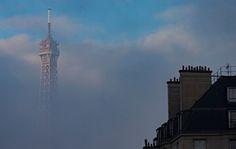 Luz solar do amanhecer ilumina o topo da Torre Eiffel, uma vez que emerge das nuvens de baixo pendurado em Paris