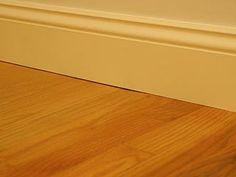 Gap between traditional baseboard and wood flooring.