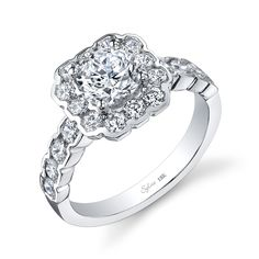 The bezel-set halo in Sylvie's engagement ring enhances the center diamond & resembles pretty flower petals.