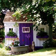Tiny garden house tucked perfectly beneath a tree with purple accents...love the tub full of flowers!