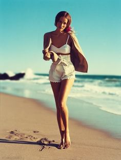 Scalloped high waisted shorts, white bikini and tan long sleeved sweater.  Beach outfit.