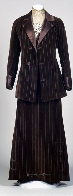 Brown striped velvet suit ca. 1912, with plum-colored satin inserts. Satin sash at waist. Applications of needle lace on dress bodice and embroidered tulle guimpe. Costume Gallery of the Pitti Palace via Europeana Fashion