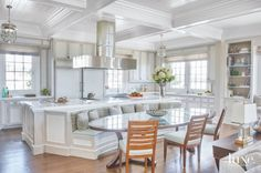 In the kitchen, Ruderman prepared for large family gatherings with a custom banquette built into the back of a curved island teamed with an oval glass-and-walnut table. A decorative painter finished cabinetry in a distressed taupe and cream, and the designer maintained these neutral tones in the adjacent family room, which boasts a stone replace wall. Calacatta Caldia marble tops the kitchen's 4-by-14-foot island, which has curved banquette seating built into it. A custom oval table from ...
