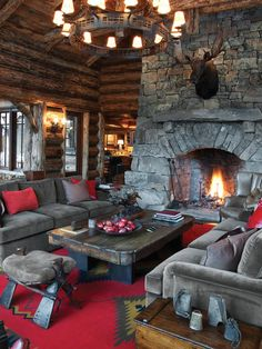 Two comfortable couches and a large wooden coffee table center on a massive stacked stone fireplace in this rustic lodge.