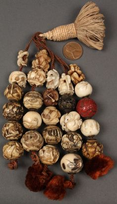 Collection of 26 Asian ojime beads,carved from ivory, bone, celluloid,cinnabar strung on a tassel depicting a tiger , skull, devil faces, rats , flying crane, butterfly . | These were all collected by George and Charles Mitchell during the course of several trips to China and Japan in the late 19th century.