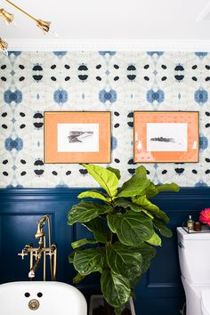 Jenny from Little Green Notebook was inspired to remodel her bathroom when she found this gorgeous navy blue and cream abstract wallpaper. Jenny used a coat of Opera Glasses for the wainscotting to complement the deep blue in her wallpaper. Peach, green, and gold accents complete the rest of this modern design scheme.