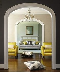 Yellow and grey living room. Not sure what the cushion is doing on the floor - but whatever!