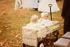 Such a cute entrance wagon to welcome the bride! Photo by Kelly T. #minneapolisweddingphotographers #weddingceremony #flowergirls