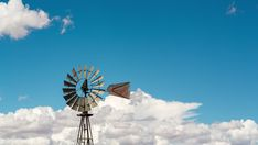 A static medium daytime timelaspe shot of a windmill frantically blowing in the wind against a bright blue sky with cumulous clouds, front view. A 17, Windmill, Hd Video, Geology, Stock Footage, Wind Turbine, South Africa, Shots, Clouds