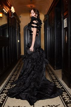 Just before walking the carpet at tonight's Met Gala, Dakota Johnson in a Gucci custom black silk moiré gown featuring duchesse satin straps and 3D flowers with a full pleated taffeta and duchesse satin ruffle skirt, and a black lurex and silk jacquard evening clutch.