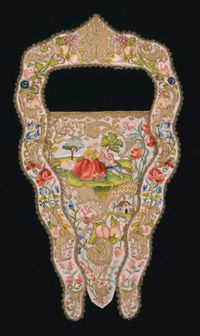 Stomacher and Collar    This stomacher has an unusual matching collar to frame the neckline and further emphasize the taper of the torso. The pictorial motifs on the stomacher and collar are the height of Rococo refinement. In the asymmetrically placed main scene, a sheep sits contentedly as a shepherdess crowns her gallant with a floral wreath. An abundance of fruit and flowers and a tiny out-of-scale building add to the idyllic fantasy.    Possibly made in Italy  c. 1730-40