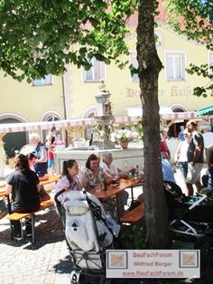 Musikprob Brass Festival Pfullendorf, Seepark BauFachForum Baulexikon Thema: Brunnenfest 2017 in Pfullendorf. Die Musiker proben bereits auf den Großen Auftritt. Die Gäste feiern unter den Bäumen um den Brunnen herum.