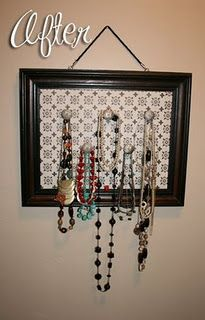 Jewelry organizer made out of a picture frame, cardboard, scrapbook paper, and some knobs.  Cute!