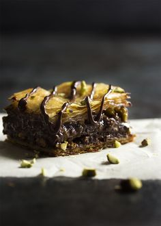 This chocolate baklava is packed full of pistachios and bittersweet chocolate, then drizzled with a honey syrup to make wonderfully rich Greek dessert!   justalittlebitofbacon.com