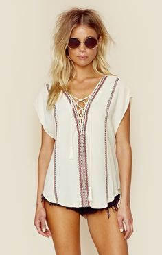 """ASTR The Label's Esperanza Top features intricate cross-stitched embroidery, lace up detailing with tassel tie closure, and a crepe rayon fabrication.   ImportedDry Clean OnlyRayon ViscoseFit Guide:Model is 5ft 7 inches; Bust: 32"""", Waist: 24"""", Hips: 34""""Model is wearing a size XSRelaxed FitShoes Featured Not Available For Purchase"""