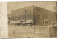 ID#0190. Date: c1890-1900. This is a photo of the Park Hotel from the southwest of College and Main Streets. What can be seen of the products in the display case indicate that they are from a drugstore. The first drug store at this corner location was the Oberlin Pharmacy which opened in 1890. The dresses of the women in front of the hotel appear to be from the late 19th century. Participant: Charles Bailey.