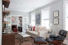 Designer Justine Sterling set out to modernize this young bachelor's open living and dining areas, but in a thoughtful way that would respect the location and also provide the client with a functional design. The narrow living room space was one of the biggest challenges in the space planning. By creating a wall hung entertainment unit and bookcase, with a large area rug and small cocktail tables, the narrow space was visually widened.  Sterling's client has a great sense of nostalgia for…