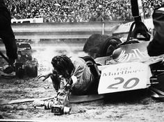 An incredible shot of of a Formula 1 crash, having taken out a trackside photographer. Note the camera on the ground in front of the car.