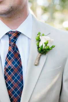 Men's boutinere white rose, green berries tied off with twine.