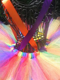 Ce tutu adorable et lumineux est parfait pour les costumes de clown! Il est fait avec du tulle rouge, orange, jaune, vert, bleu et violet. Ruban et boutons colorés embellissent la façade de votre tutu et rubans de satin sont attachés pour créer des bretelles. Ceux-ci sont