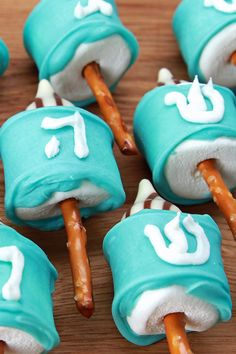 Dreidel PopsIngredients- 1 bag marshmallows pretzel sticks chocolate kisses (hugs were used in this  recipe 1 cup white chocolate chips 4 drops blue food coloring white frosting