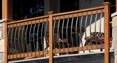 This deck railing consists of wooden posts and rails with curved aluminum spindles.
