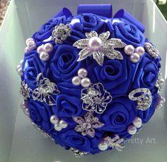 Buquê de flores azul royal em cetim com broches prateados e pérolas.  Os buquês são personalizados e montados de acordo com o gosto da noiva.  Eles são únicos sendo que nunca existirá um buque idêntico ao outro.  Composto de broches em tons de prata cravejados em strass, flores de cetim e pérolas.