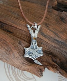 This Thors Hammer pendant symbolizes the battle between Thor and his enemy Jörmungandr. In Norse mythology Jörmungandr is a serpent that encircles the world, destined to face the Thunder God at Ragnarok.  This is an original design created by Kevin. It was cast in sterling silver and set with an amber cabochon stone.  The pendant is 2 by 1 1/8 inches and comes strung on a brown leather cord. It is an adjustable length and will fit over a large mans head.  We have many variations availabl...