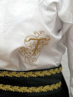 """Embroidery """"t"""" on a white blouse"""