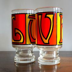 Vintage 1970s Retro LOVE Glasses. Two (2) Red & Yellow print tumblers. Kitsch, psychedelic print. Sweet Valentines Day, Anniversary, Wedding gift! Gas station promotion glass. Footed highball glasses. Perfect for kitchen or bar. I believe these to be S & H trading stamp glasses, similar to the Mandalay Dancer glasses. Well weighted, thick bottom, crystal clear glass. Excellent vintage condition, with no color loss. | Shop this product here: spree.to/ace2 | Shop all of our products at…
