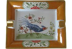"""Exquisite Hermès porcelain ashtray. Beautiful chinoiserie motifs within a pumpkin border. Central figure of a sprightly red-faced blue bird with resplendent plumage. Rich gilding on rims and all four exterior sides. Underside lined in green suede. Marked """"Hermès Paris"""" and """"Made in France""""."""