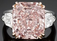 No subtlety here: a large pink diamond with more diamonds on either side - 7.09 carat Fancy pink diamond, an incredibly rare stone of exceptional quality. And it's flanked on either side by two shield or bullet-cut diamonds, totaling 1.04 carats and both graded E color and VS1 clarity.  - engagement?