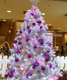 White Christmas tree with purple and pink bulbs.