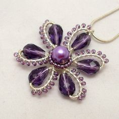 This pendant is made with silver plated wire, purple glass teardrop beads, and Czech seed beads. This flower pendant is one of my signature I don't think it would be too difficult to do something similar to this with tatting.Trendet e Modes me te reP Wire Wrapped Jewelry, Wire Jewelry, Jewelry Crafts, Beaded Jewelry, Jewelery, Handmade Jewelry, Flower Jewelry, Bullet Jewelry, Gothic Jewelry