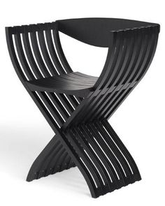 CURULE CHAIR BY PIERRE PAULIN This 1980s design takes its X form and name from a Roman folding chair, which has been re-imagined in black-stained beech with a leather backrest. A natural beech version is also offered.  $1,330; ligne-roset-usa.com