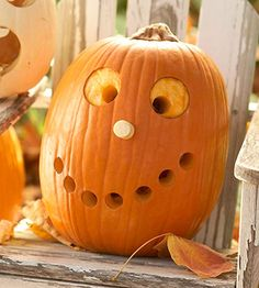 "Create a goofy grin on your pumpkin by using an apple corer to punch perfectly round circles. The punched plugs can be used for additional features; here, the white nose is a plug from a white pumpkin. Scrape just the skin away around the punched ""pupils"" to create the eyes. /"