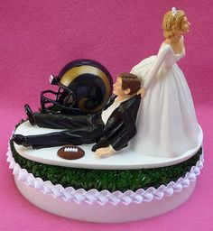 Looking for a unique and funny, yet still elegant wedding cake topper? Be the envy of every sports fan with our one-of-a-kind WedSet original and exclusive football-themed Turf Topper™! Now hes playing on your turf!  The humorous, resin-like bride and groom rest atop a 4 1/2 x 6-inch oval professional cake topper base adorned with actual artificial turf. A row of white satin-like ribbon trim around the edge of the cake topper base completes the look. The topper stands very roughly 6 inches…