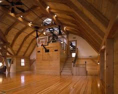 What a riot this space is. A party barn in Concord, MA; added to a wildly remodeled old carriage house. There is a very sweet inglenook seating area, just to the left of the hoop, defined by tilted posts. The forty foot span queen post trusses were designed not to interfere with basketball shots.  Fire Tower Engineered Timber http://www.ftet.biz/