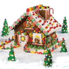"""High-Voltage Christmas Gingerbread House - Build a High-Voltage Christmas scene using a Wilton Pre-Baked Gingerbread House Kit. This design adds extra candy trims, cookie """"people,"""" and ice cream cone trees to your winter wonderland."""
