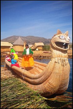 "Locals in traditional clothing and the ""totora"" boat (made of floating reeds), Uros Islands, Lake Titicaca, Peru - Uros are a pre-Incan people that live on 42 self-sustained man-made islets in Lake Titicaca, near the border of Peru and Bolivia. The Uros use the totora plant to make boats of bundled dried reeds, and to make the islands themselves."