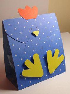 Caixinha em papel de scrap 180gr com patinhas e bico suspenso por fita banana. Com as laterais abertas e acompanha saquinho plástico, Medidas: Altura 10cm largura 4,5cm R$ 3,39