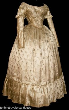 "1840s figured silk evening gown; deaccession from NY museum, lined bodice, self fabric buttons, piped at seams, back hook & eye closure, cartridridge pleated waist, side front slit pocked, attached calico printed petticoat of an earlier fabric, carcenet facing; bust: 36""; waist: 26""; 56"" from shoulder to front hem; inner sleeve seams likely resewen in period"