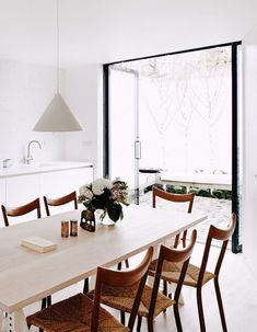 pale dining table, wooden and woven chairs, simple white pendent,white walls, black door frames