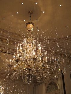 crystals hanging from clear thread surrounding the chandelier and sharing the light to sparkle,