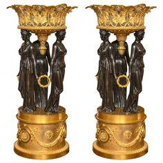 """Pair of palatial antique dore and patented bronze figural planters.   A pair of planters in the form of reticulated gilt bronze grape vine baskets supported by dark patinated bronze winged caryatids. The caryatids are joined at the hands by gilt bronze wreaths and mounted on gilt bronze circular columns adorned with garland swags and masks. Measures: 34"""" H X 16"""" W.  In our Garden City Long Island location."""