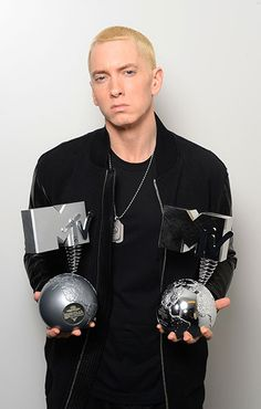 Eminem poses in his dressing room with the 'Best Hip Hop' and 'Global Icon' awards during the MTV EMA's 2013 on November 10, 2013 in Amsterdam, Netherlands.